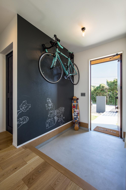 【玄関スペース】 黒板塗料を塗った壁面。ご友人が描かれたイラストがお出迎えしてくれます。