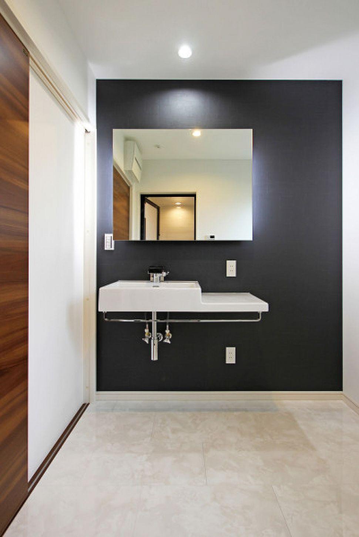 黒×白でデザインした洗面室。鏡の裏に照明器具を配し、上質な空間を演出。