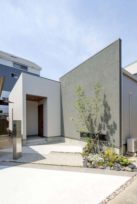 タイル×アクセントのグレーの塗り壁。木目調の軒天と玄関扉が効いています。