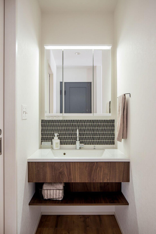 玄関ホールに設けられた洗面台。中央に貼った個性的なタイルが空間のアクセントに。既製品と造作を組み合わせて機能性とデザインにこだわりました。