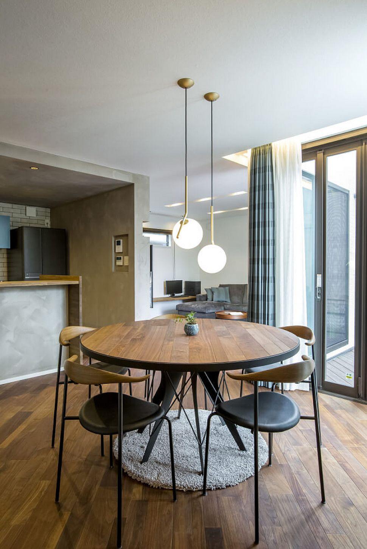LDKの床はウォールナットの無垢床。目線の動きと合わせるよう、床材を斜めに貼ったのがポイント。テーブルは床に合わせて作った造作。天板の貼る方向も床に合わせたというこだわりぶりです。ダイニングの照明はお気に入りのFLOS「ICLIGHTS」。