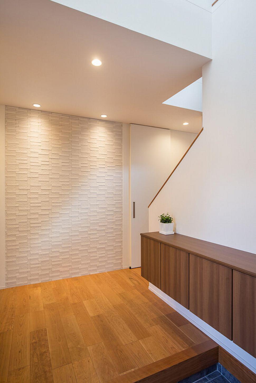 玄関正面には空気を美しく整えてくれるエコカラットを。タイルの厚み分壁をへこませて埋め込んでいるためスッキリ仕上がりました。