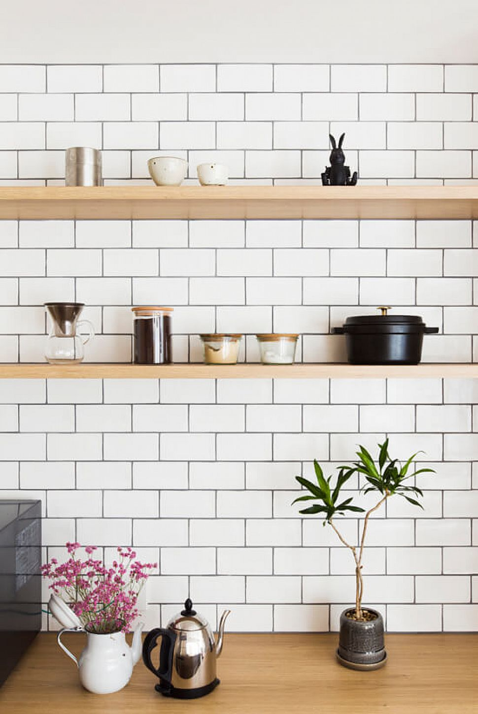 キッチン背面の壁もタイル張りに。棚に置かれたキッチングッズが映えます。