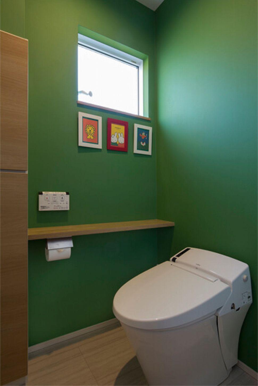 【トイレ】 お気に入りの絵本をイメージした鮮やかなグリーンの壁紙で遊び心をプラス。壁に掛けた絵がよく映えます。