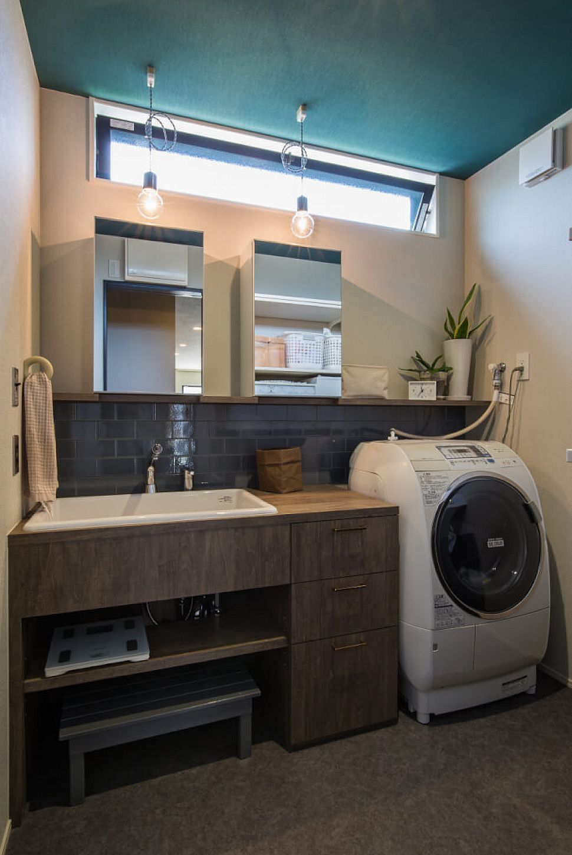 【洗面室】 洗面化粧台も造作しました。大型の洗面ボウルを入れて収納も多くとりました。ダークグレー色のモザイクタイルがヴィンテージ感を出しています。お住まいの中で洗面室の天井にだけ唯一鮮やかなグリーンの壁紙を採用し、遊び心を感じる暮らしのアクセントになりました。