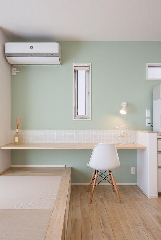 【スタディコーナー】 カウンターは椅子でも、タタミコーナーからの座卓としても使うことができ、家族のコミュニケーションが増えるよう工夫されています。カウンター正面には白を基調とした3面状ミックスのガラスモザイクタイルを貼り、グレーグリーン色の壁紙ともいい相性です。スタディコーナーでは、奥様がキッチンで家事をしながら近い距離でお子様の勉強を見てあげることができます。