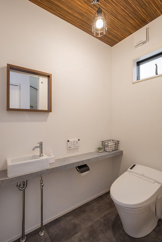 【トイレ】 手洗いのカウンターにモルタル調のメラミンを使って、少し男っぽいイメージの1Fトイレ。