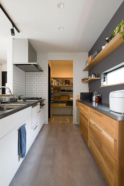キッチンはグレーの天板に、背面の収納はステンレスの天板にと素材や色味にもこだわったキッチン。奥には、通り抜けるパントリーがあり、使い勝手もとても良い。