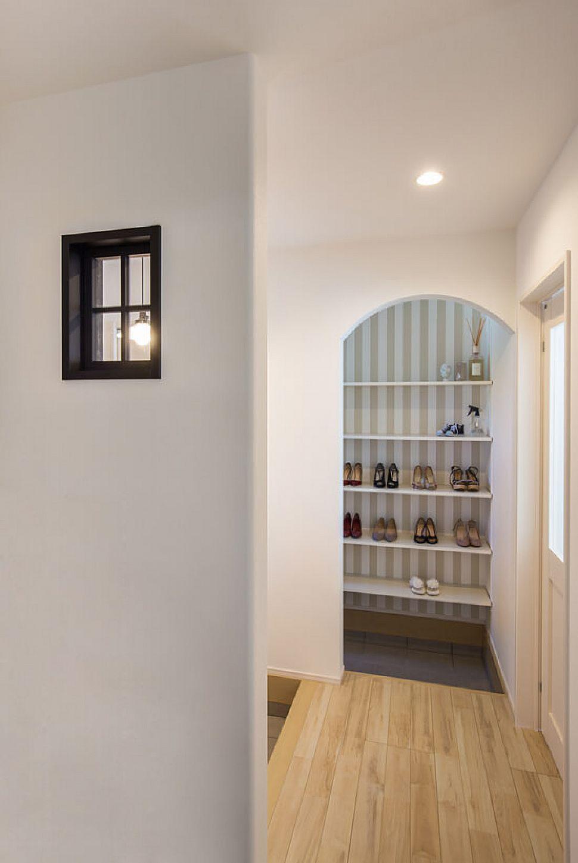 【玄関ホール】 玄関の壁にあしらった黒の小窓と、アールの垂れ壁から覗くシューズクローク内のストライプの壁紙が、まるでお洒落なショップを思わせるモダンな印象。