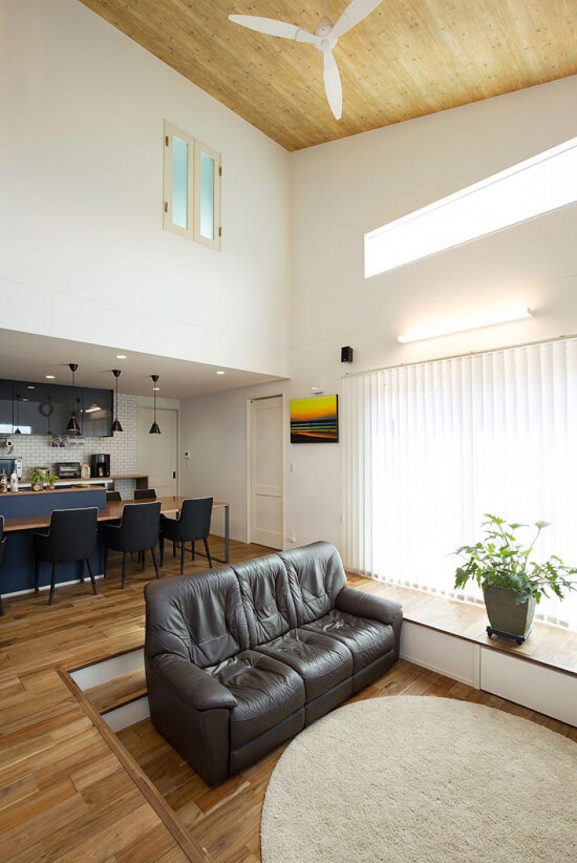 吹き抜けのあるリビング。勾配天井を配し、リビングの床を下げることで、開放的な空間になりました。2階のお子様部屋にはリビングとつながる吹き抜け窓を配置。家族の存在を感じることができるため、自然とコミュニケーションが増えます。
