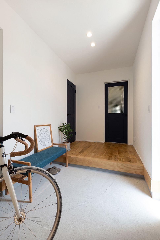 【玄関スペース】 玄関床はモルタル仕上げ。モルタルの自然なグレー色とオークの床材は相性抜群です。土間を広くとることで、自転車を置いたり、ベンチを置いてくつろげるスペースになりました。