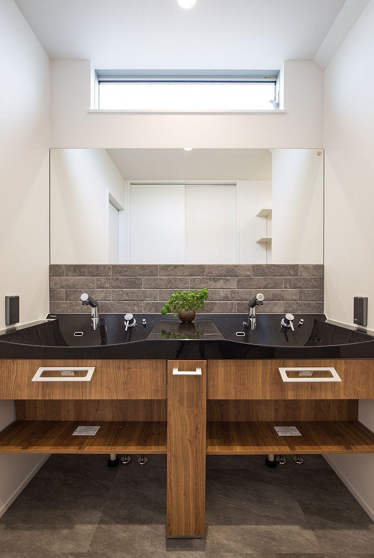 【洗面室】 2ボウルの洗面台をセレクト。2人並んでも広々と使用できます。ブラック×木目に、凹凸のある自然石風のタイルを施し、ラグジュアリーな空間を演出。