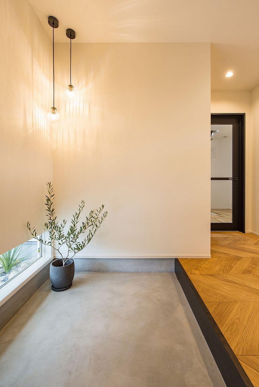 【玄関ホール】 ヘリンボーンの床材をブラックで引き締めた玄関。ペンダントライトで照らされたグリーンがお出迎え。