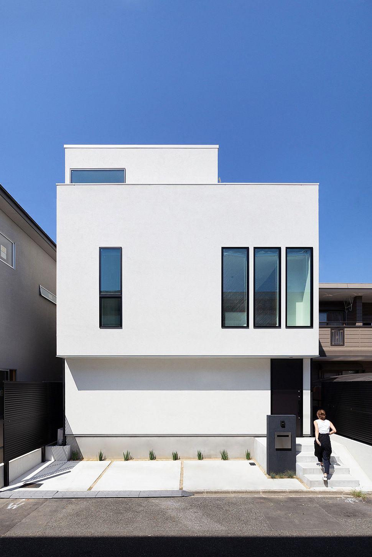 【外観】 シンプルなライトグレーの塗り壁が特徴的な3階建ての住宅。3階部分をセットバックさせ、ボリューム感が大きくなりすぎないようにまとめました。