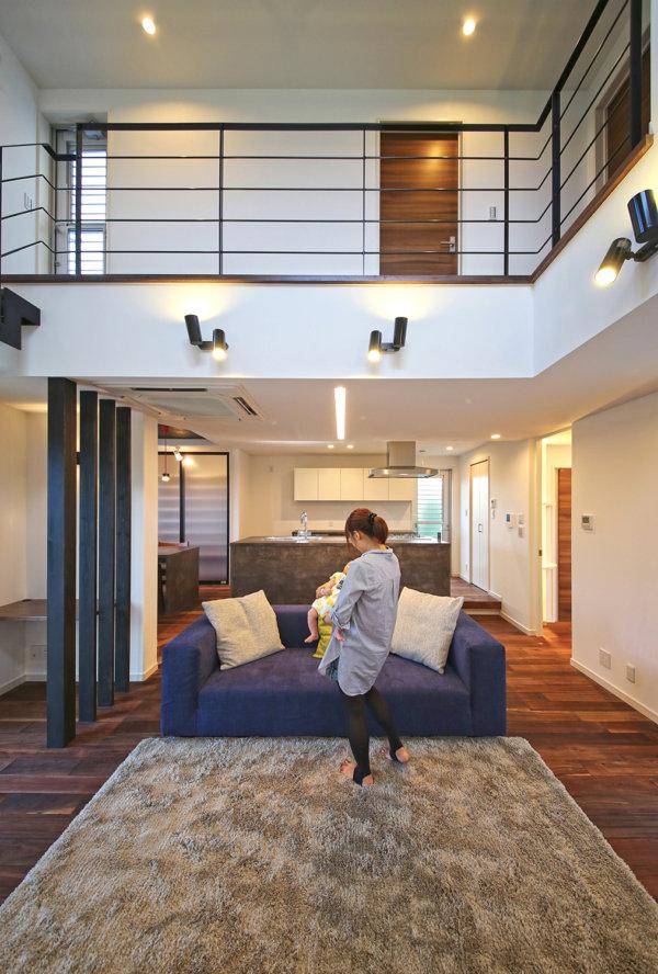 窓のない外観からは想像できないほど開放的な室内。床材は無垢のウォルナットを採用、モダンな空間を演出。