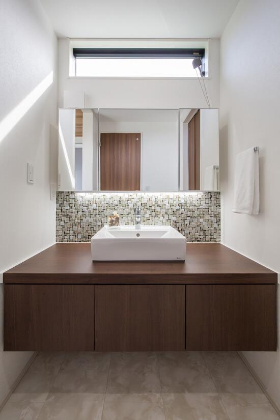 こだわりの造作洗面台。鏡下の間接照明が綺麗にタイルを照らしてくれます。