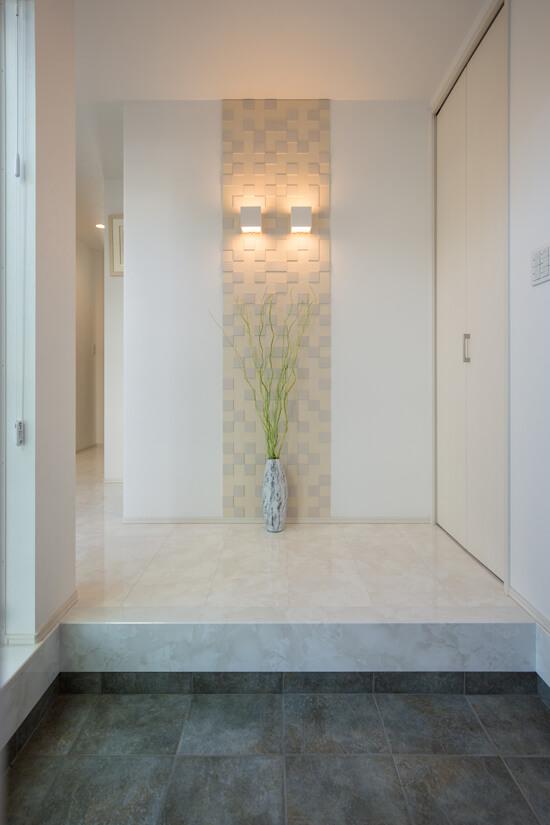 玄関の正面のエコカラットは、機能面だけでなく照明をプラスすることでより上質な空間に。