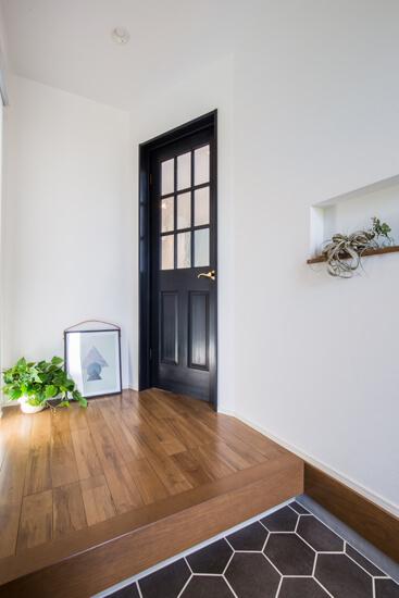 玄関タイルには黒のヘキサゴンタイルを。黒色の扉とあわせて、シンプルながら印象的な玄関に。