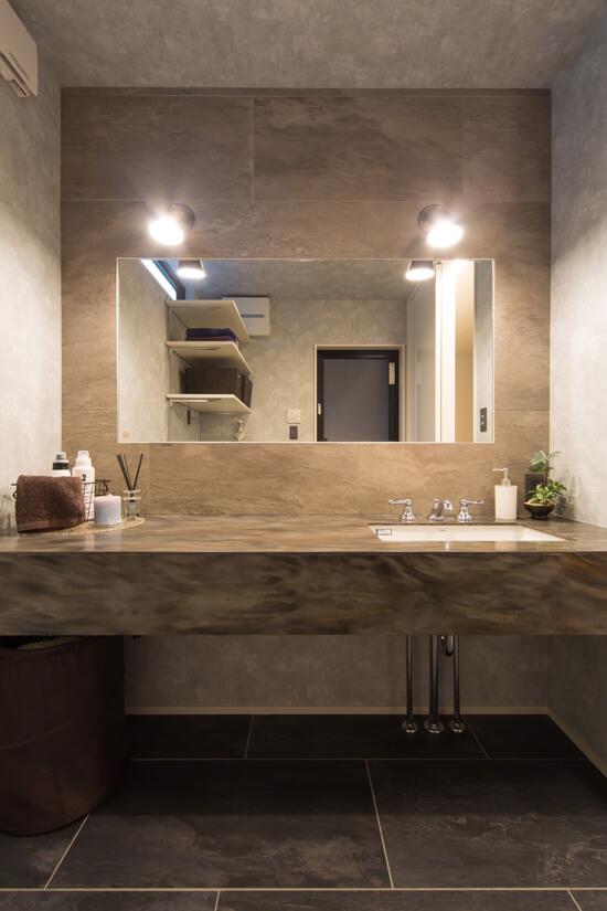 大理石を使用した造作洗面台、グレーとブラックのタイルで統一された高級感あふれる空間に。