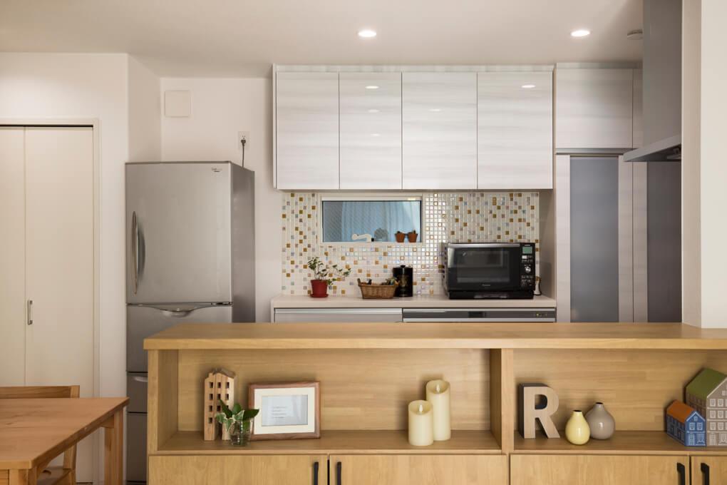 【キッチン】 キッチン手前は造作収納を設置。オープンな飾り棚と扉付の収納で、「見せる」と「隠す」を両立しました。キッチンファニチャー奥に貼ったモザイクタイルのオレンジ色がキッチンに彩りを添えています。