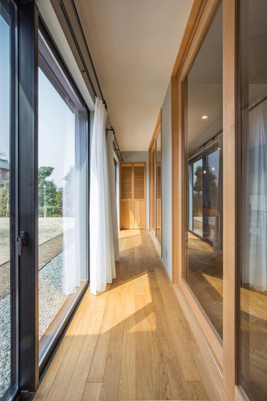 【縁側】 日本古来の家屋文化である「縁側」を設けました。室内の明るさを保ちつつ、夏場は暑くなりすぎない快適な空間が実現。縁側の床はオークの無垢材を、正面の収納の建具にも無垢材を使用し、自然素材の優しさと日差しの温もりを感じる癒しのスペースに。縁側は日本の四季を感じ、楽しむ、特別な空間です。