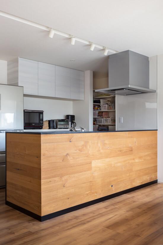 【キッチン】 床の色味に合わせたチーク材をキッチン対面側の腰壁に貼りました。笠木と巾木をブラックにする事で空間を引き締めました。