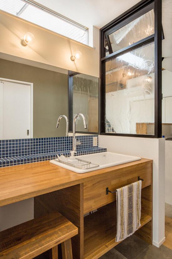 洗面は造作で使い勝手も見栄えもよく。洗面横の造作ガラス壁は、アンティーク調ガラスを施し、木枠を黒色で塗装。視界は遮らず、程よく空間に区切りを設けました。