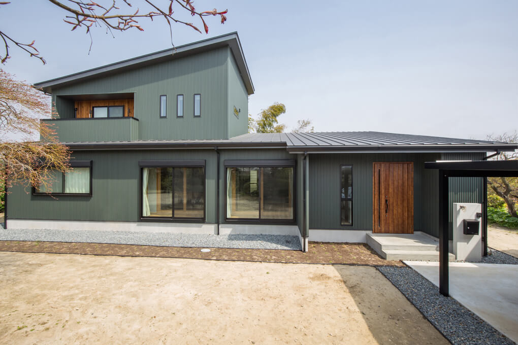 【外観】 外壁はモスグリーンのガルバリウム鋼板と木質系外壁(レッドシダー羽目板)の組み合わせが相性が良く、落ち着きのある、ナチュラルモダンスタイル。広い敷地を贅沢に活かしたゆとりのある佇まいに、屋根は片流れを採用し、シャープで迫力がある印象になりました。