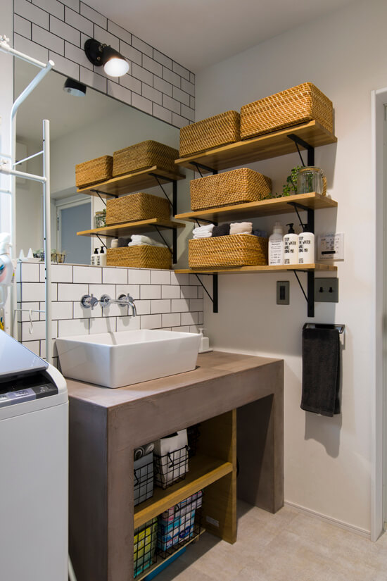 キッチンカウンターに使⽤したモルタルを造作の洗⾯台にも使⽤。壁は、⽩いタイルにグレーの⽬地。壁付の⽔栓やスクエアなボウル、照明のアメリカンスイッチなど、⼀つひとつにこだわりを感じる、T邸にしっくり馴染む仕上がりだ