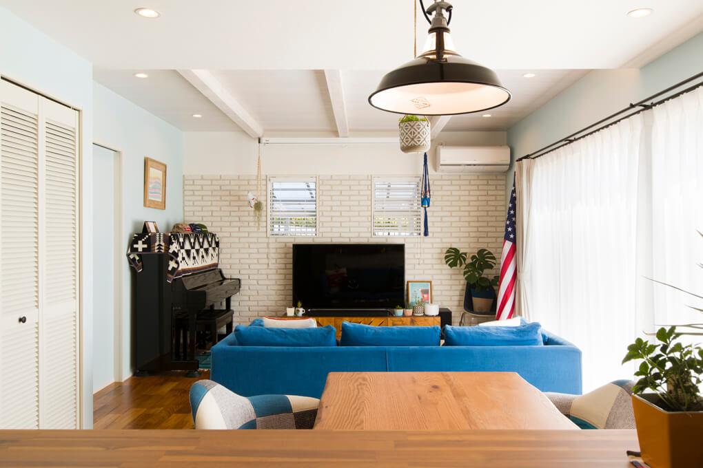 床に使ったチークの無垢材などの木の色と、白を基調にした室内に、鮮やかなブルーのソファや雑貨が映える。
