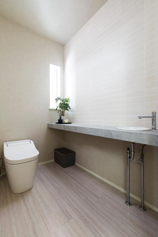 トイレも白を基調に、シンプルですっきりとしたデザインに。グリーンが映える造作の手洗いカウンターや壁のタイルが程よいアクセントに