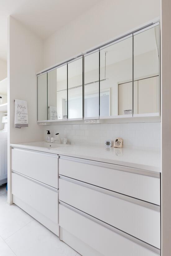 清潔感のある白いタイルが似合う、洗練された洗面スペース。