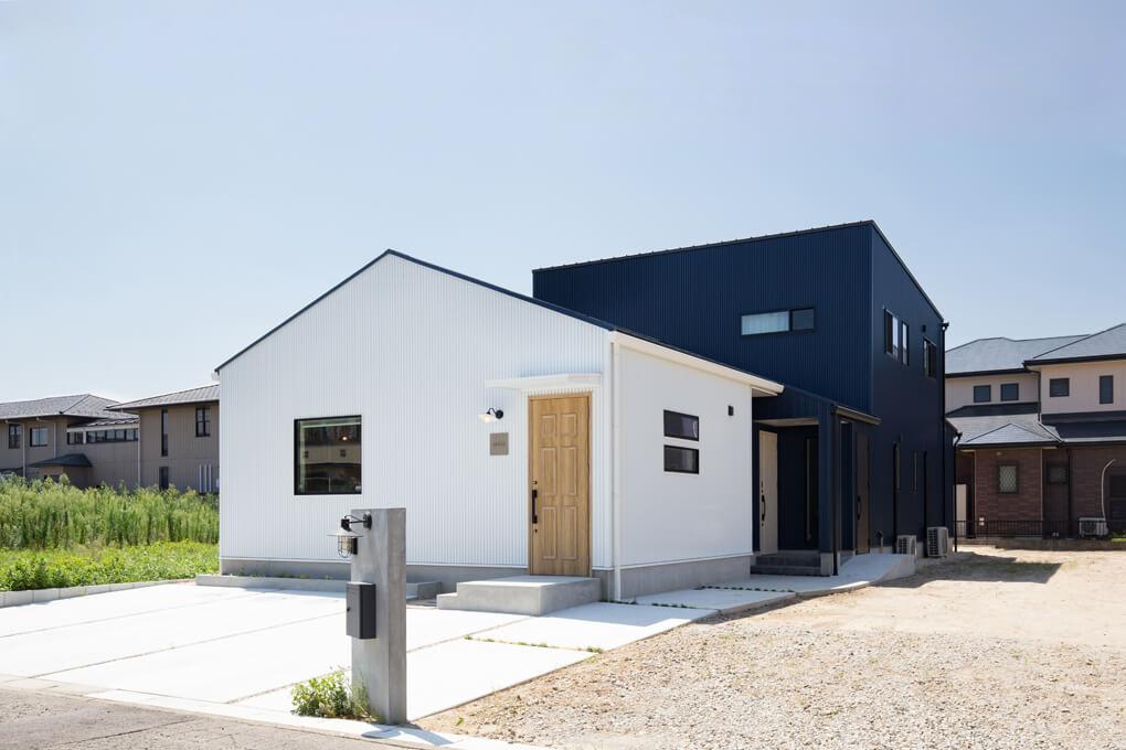 切妻の平屋部分の奥にBOX型の2階建てを組み合わせた建物。異なる形と異なる色で奥行感を演出しています。