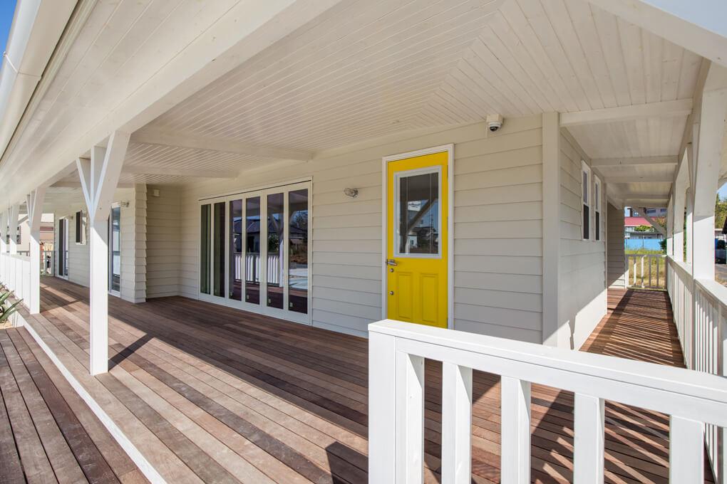 【カバードポーチ】 外観はシンプルにホワイト一色でまとめ、玄関ドアだけ色味を持たせ、ミッドセンチュリー思想を取り入れました。カバードポーチはあえて広く設計し、庭や隣地との距離感を穏やかに感じることができます。