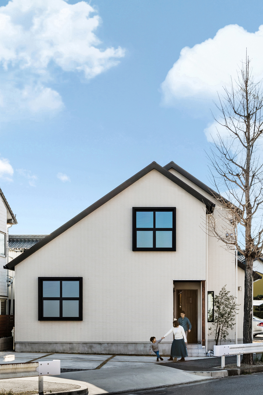 【外観】 三角屋根の可愛いシルエットに、大きな四角の窓をシンボルとした外観。外壁には白色のタイルを使用し、玄関周りの木貼りや表し柱がナチュラル感をプラスした、甘すぎないナチュラルモダンな印象に。