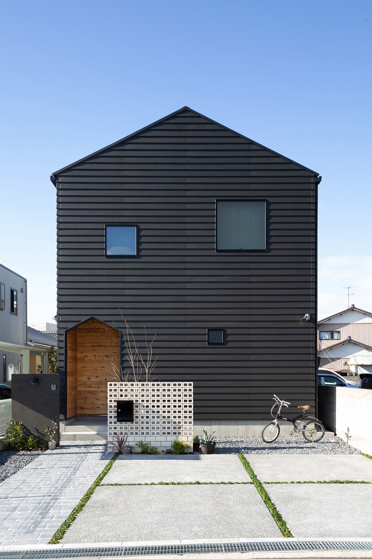 【外観】 黒色のラップサイディングの外壁に、三角屋根の可愛いフォルムが印象的。ランダムに配置された正方形の窓がリズムを生み、遊び心をプラスした個性的でモダンなファサードとなりました。