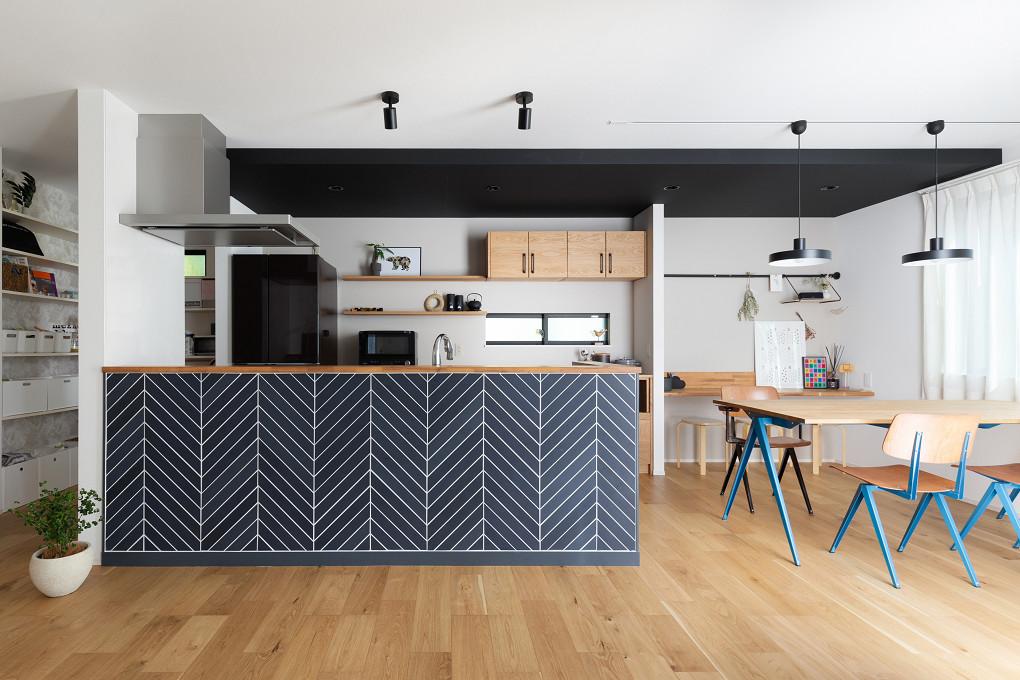 【ダイニング・キッチン】 回遊性をもたせたキッチン。ダイニング・キッチンに設けた下がり天井や、キッチン腰壁にタイルのヘリンボーン貼りを施し、黒のアクセントを効かせた空間に。