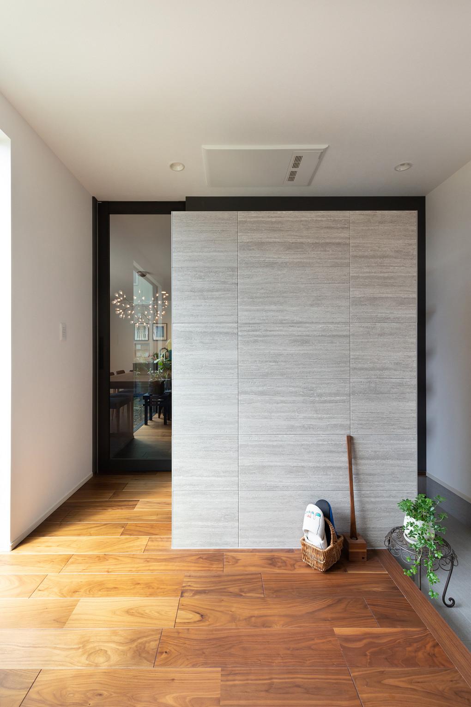 【玄関ホール】 玄関ホールに施したエコカラットが印象的。LDKへとつながるドアは、天井まで高さのあるガラス戸を採用し、すっきりとした空間を演出しています。