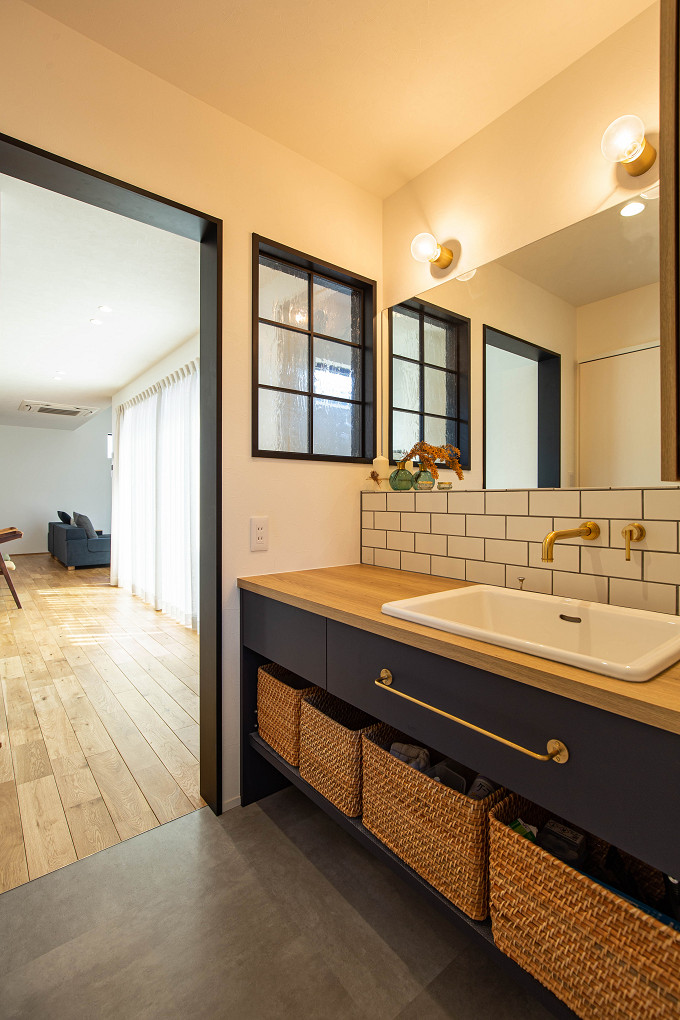 【洗面室】 水に強いメラミン製の造作洗面台。鏡の下にはタイルを施しています。洗面台の横に設けた室内窓がアクセントに。