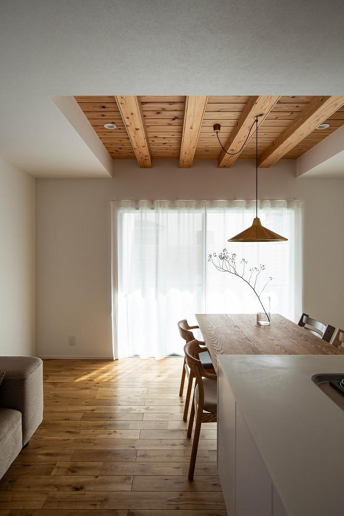 【ダイニング】 ダイニングの上部には構造梁を表し、梁と折上げ部分の天井には杉の羽目板張りを採用。ダイニングには真鍮のペンダントライトを採用し、素材感をプラスしています。