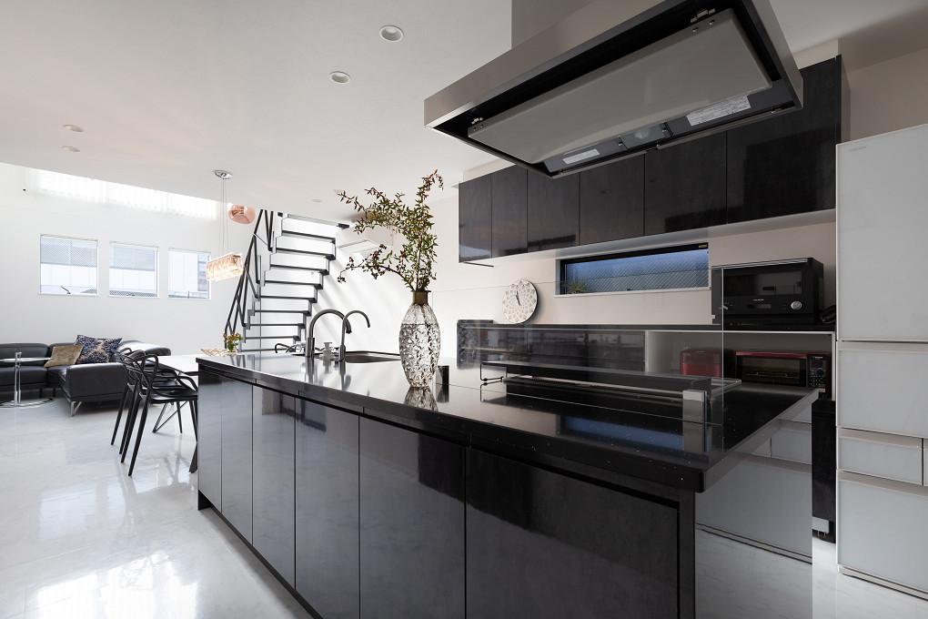【キッチン】 全体をモノトーンでまとめたモダンなインテリア。中央のアイランドキッチンの黒とホワイトの床のコントラストが美しいバランスを生んでいます。
