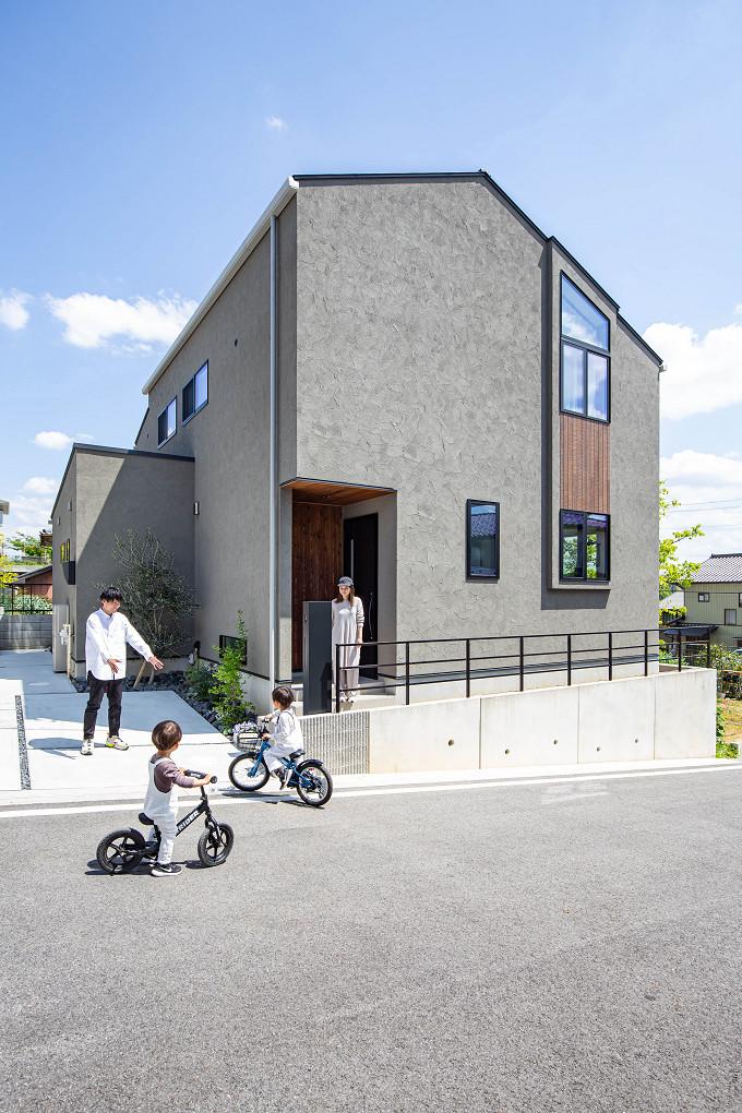 【外観】 左右非対称の切妻屋根に、木目と組み合わせて配置された連段窓がアクセントの外観。アースカラーの塗り壁と黒のサッシで落ち着いた印象に。