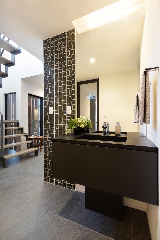 【洗面台】 ブラックのモダンな洗面台。タイルと組み合わせて高級感を演出することで、玄関ホールにマッチした自然な仕上がりに。