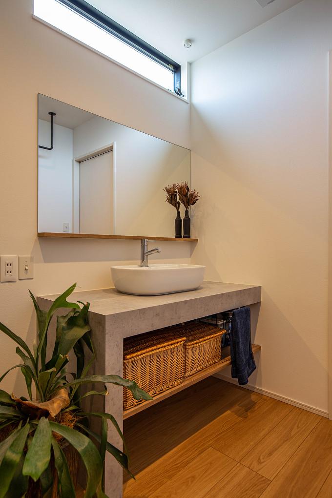 【洗面室】 モルタル調のメラミン化粧板をセレクトした洗面室。シンプルなフレームの鏡と相まって、素材感が引き立つ設えとなっています。