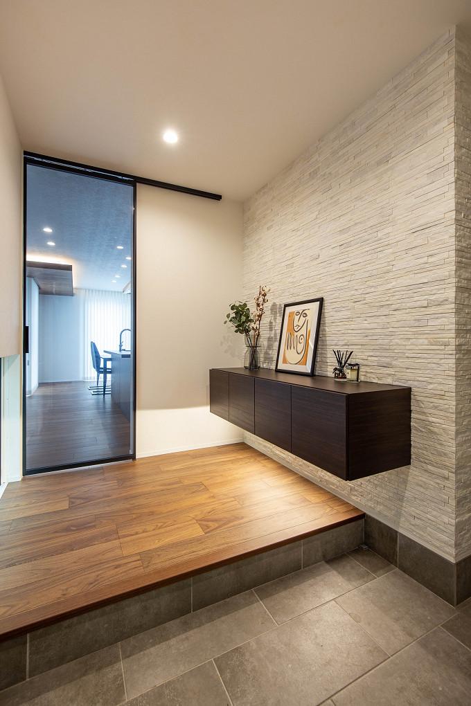 【玄関】 壁面に石を貼った重厚感のある玄関スペース。収納はフロートタイプを、リビング扉はガラスのハイドアを採用しました。